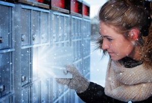 Pretty Woman Looking at Highlighted Mailbox in Winter - RF Stock Photo